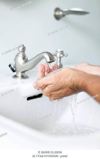 Man cupping hands beneath water running from bathroom faucet