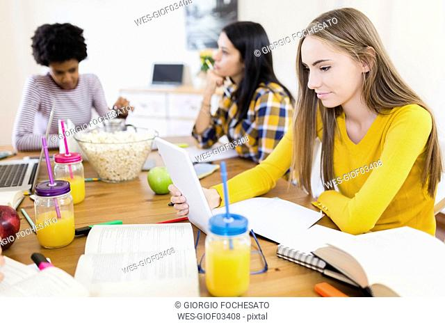 Young woman with friends using tablet at home