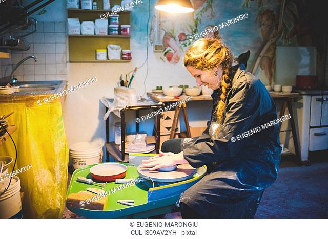 Side view of young woman sitting in workshop using potters wheel, looking down smiling