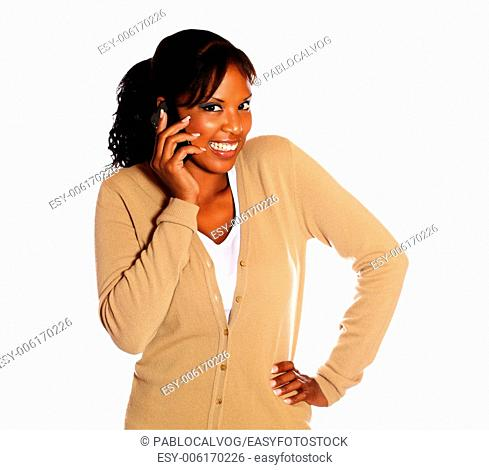 Happy young woman looking at you with cellphone on isolated background