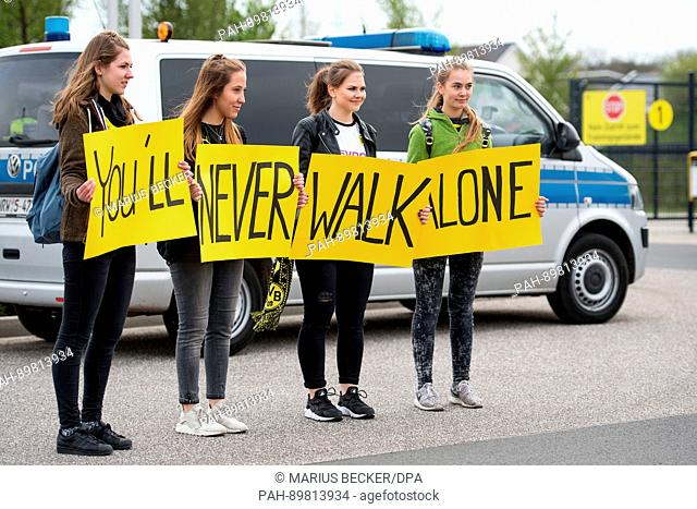 dpatop - Fans hold up signs reading 'You'll never walk alon' at the training grounds of Borussia Dortmund in Dortmund, Germany, 12 April 2017