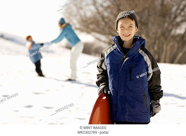 A boy holding a sledge in snow, and a mother and child behind him