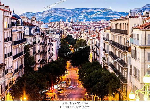 France, Provence-Alpes-Cote d'Azur, Marseille, Street in city, mountain in background