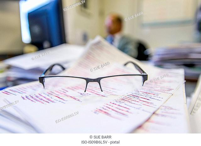 Pair of glasses on paperwork in office, close up