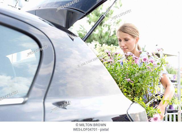 Woman loading plants in her car