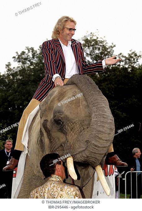 Showmaster Thomas Gottschalk riding an elephant