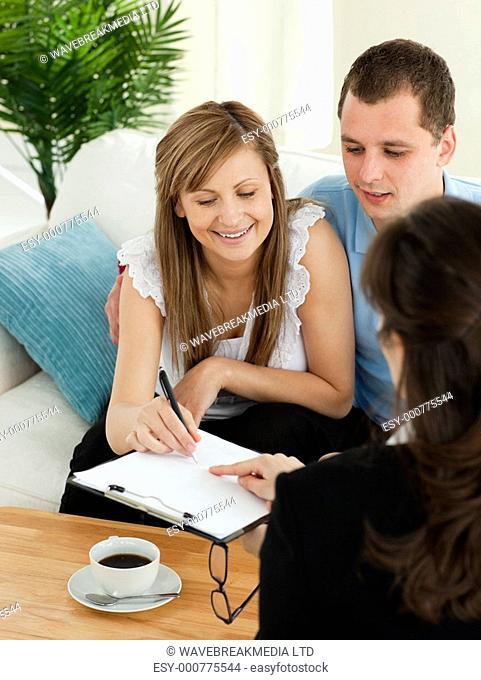 Bright young couple signing a contract sitting in their living room with a saleswoman