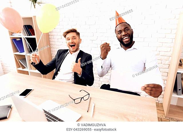 Men in business suits are sitting in a bright office in holiday caps on April 1. One of them holds inflatable balls. They are very cheerful