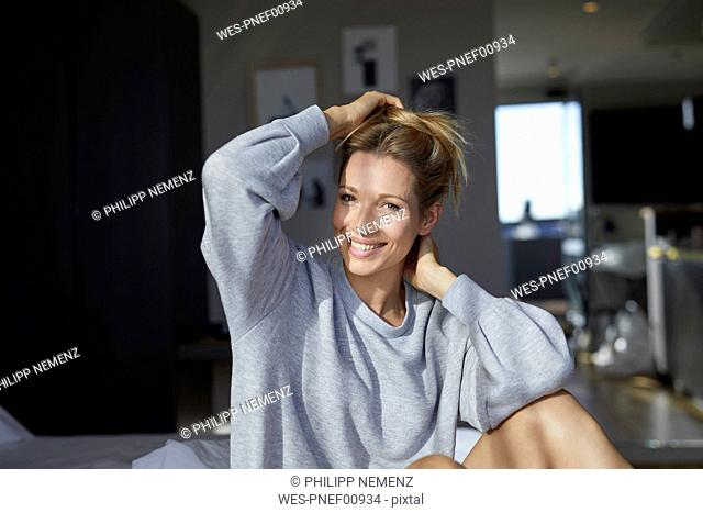 Portrait of smiling woman sitting on bed in the morning