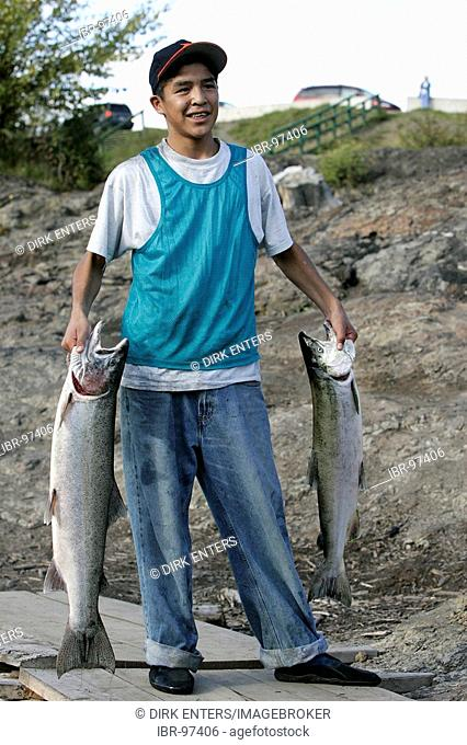 Indian with catched salmons at Bulkley River in Morristown, British Columbia, Canada