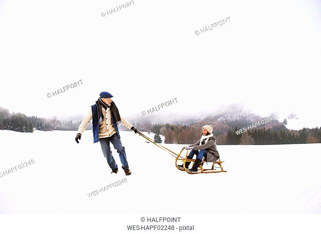 Senior couple having fun with sledge in snow-covered landscape