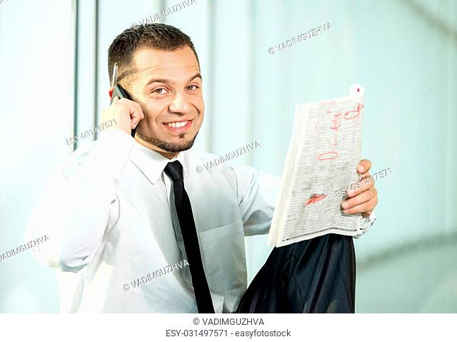 The concept of job search. A man is sitting with a newspaper and speaking by phone