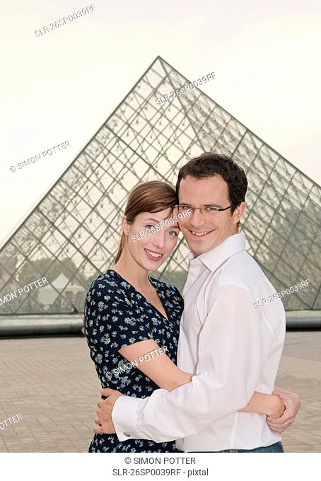 Happy couple embrace at the Louvre Paris