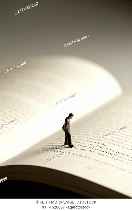 a small figure of a man walking on an open book - conceptual image for literacy and reading