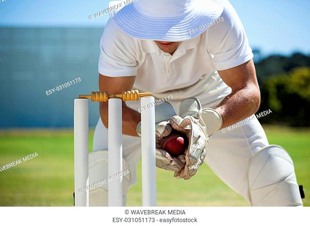 Wicketkeeper catching ball behind stumps