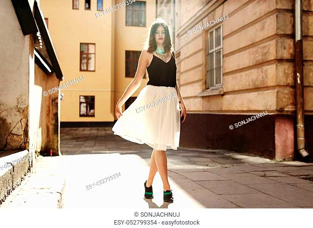happy stylish woman dancing in sunlight at old european city street, luxury look, space for text, moment of carefree and true happiness