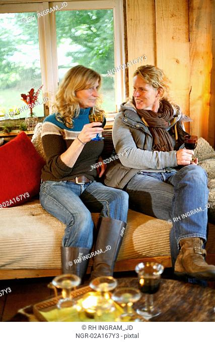 Two women relaxing in a converted barn