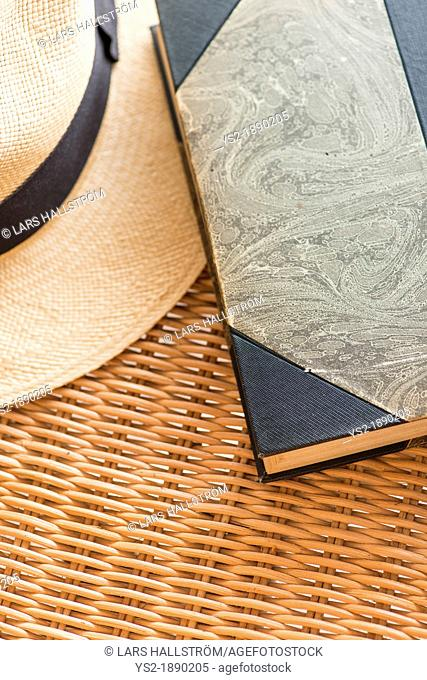 Vintage book and classic straw hat lying on wicker chair