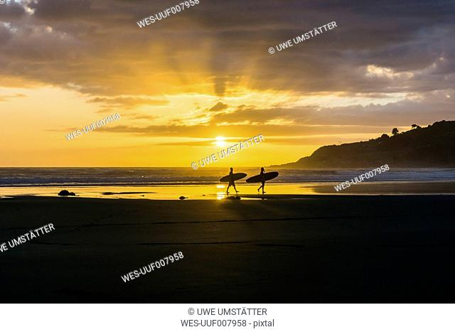 Silhouettes of two people with surfboards on the beach at twilight