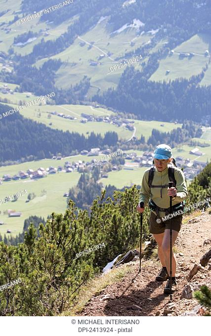 Female hiker on mountain trail with grassy valley below; Alpbach, Austria
