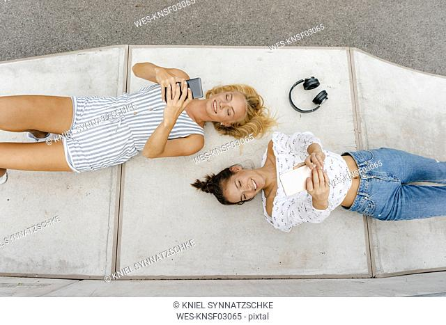 Two happy young women with cell phones lying on ramp in a skatepark