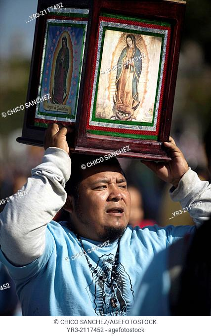 A pilgrim holds an image of the Virgin of Guadalupe as the sun rises at dawn at the pilgrimage to Our Lady of Guadalupe Basilica in Mexico City, Mexico
