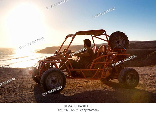 Active man driving quadbike on dirt road by the sea in sunset