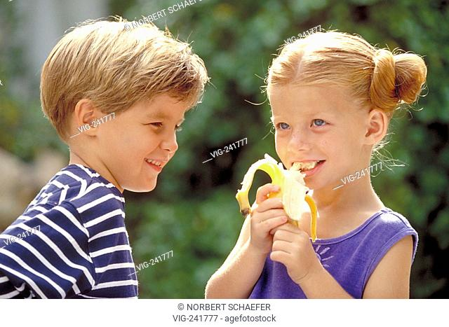 outdoor, portrait, blond boy and blond girl with blue dress, 6-8 years old, eating a banana  - GERMANY, 08/08/2004