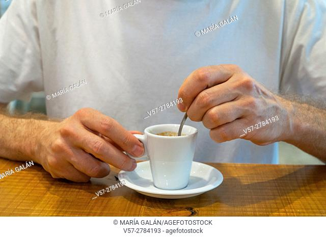 Man's hands stiring a cup of coffee. Close view