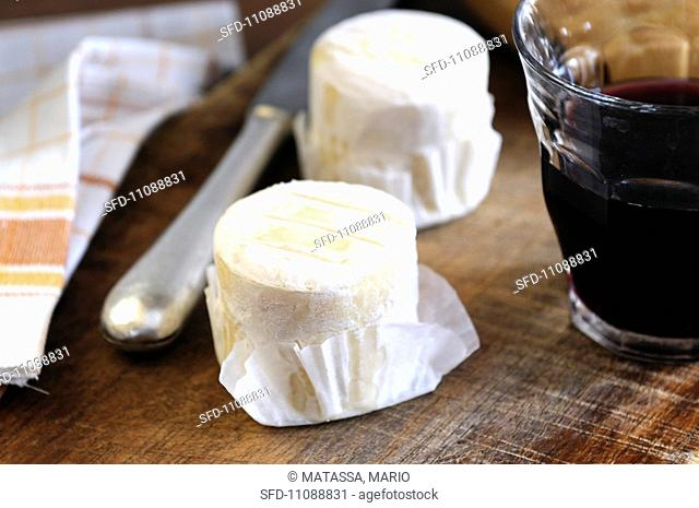 Goat's cheese on a wooden board with a glass of wine