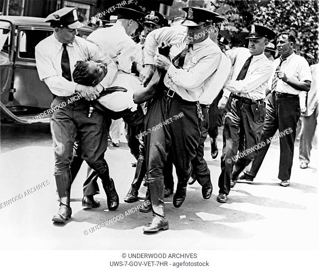 Washington, D.C.: July 28, 1932.Policemen carrying a World War I veteran, a member of the Bonus Expeditionary Forces, from a building on Pennsylvania Avenue...