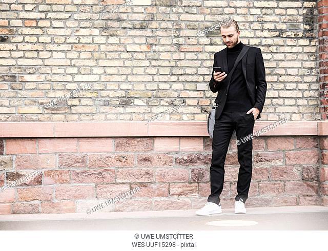 Young man standing at brick wall looking at cell phone