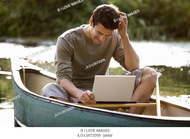 Young man sitting in a boat working on a laptop