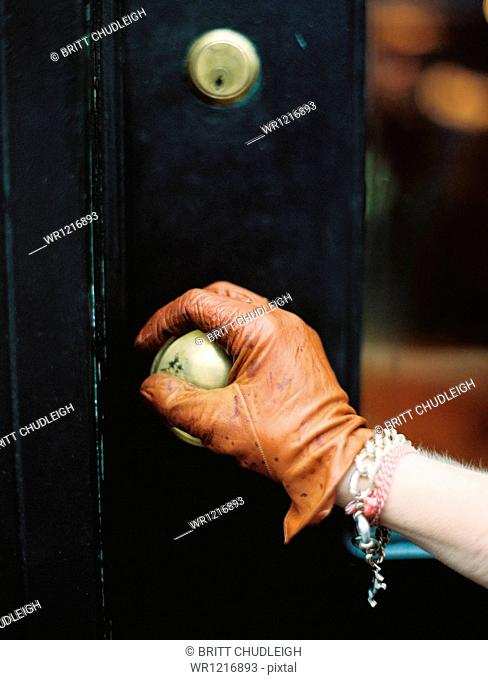 A person wearing a leather glove, opening a door