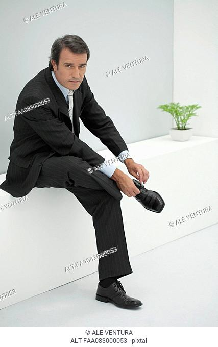Mature businessman tying shoelace