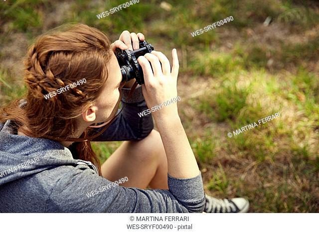 Young woman sitting on a meadow using binoculars