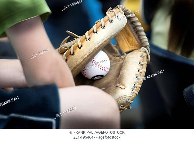 Young boy holding baseball glove with ball in the mitt
