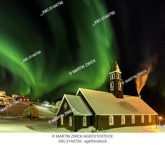Northern Lights over the Zion s Church. Town Ilulissat at the shore of Disko Bay in West Greenland, center for tourism, administration and economy