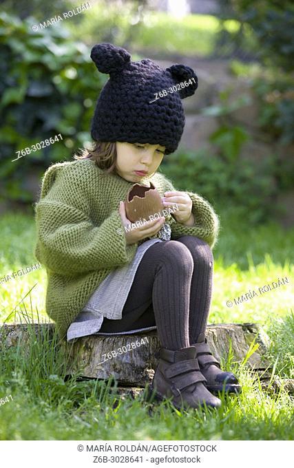 little girl eating a chocolate egg
