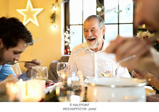 Happy senior man looking at adult son at Christmas dinner table