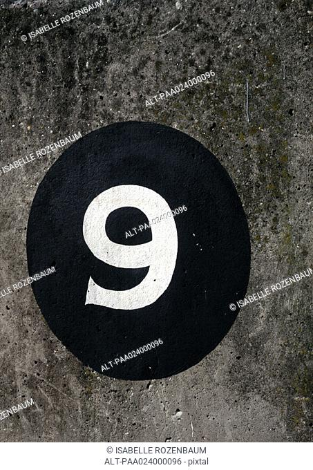 '9' text painted on black circle on rough surface