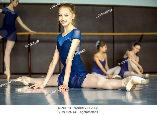 Ballerina sitting on the floor in the splits in a dance class dancers practicing on the background. Dancer is smiling