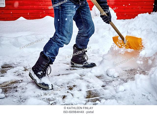 Man shovelling snow from pathway, low section