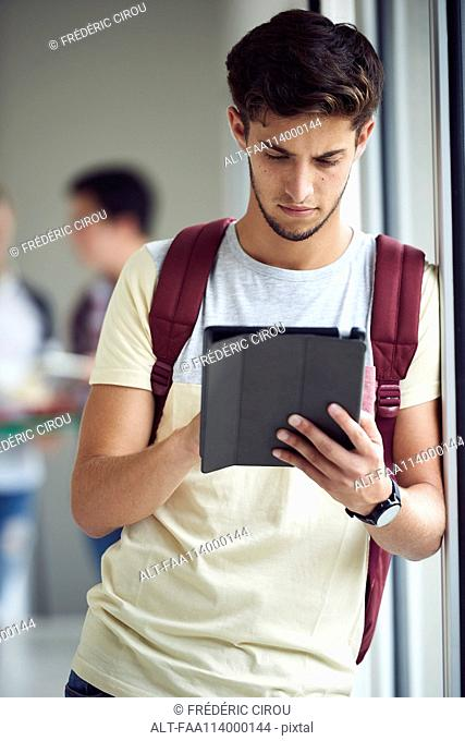 College student looking at digital tablet between classes