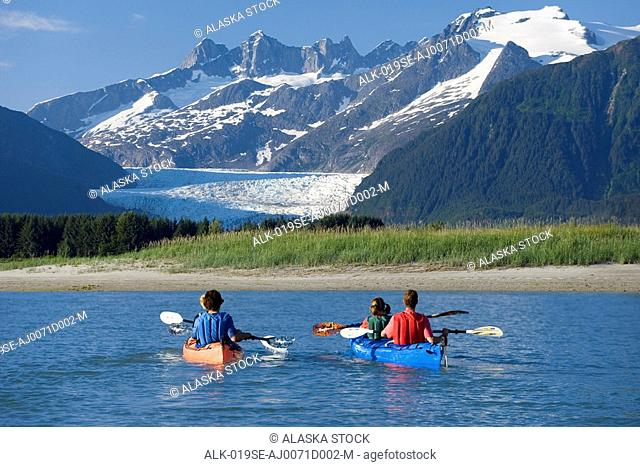 Kayakers kayaking in double sea-kayaks near Juneau in Inside Passage with view of Mendenhall Glacier Alaska