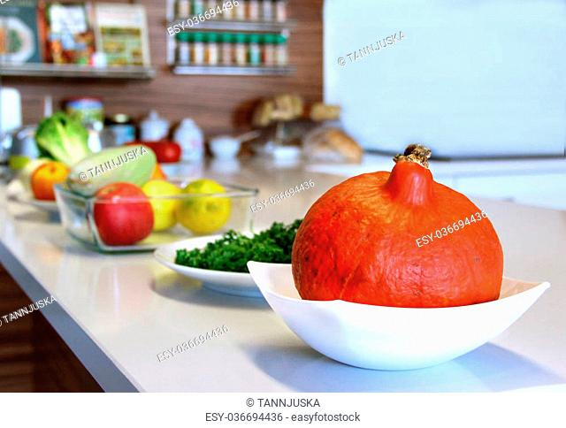 Well designed modern kitchen with a big variation of ripe fruit and vegetables on the table
