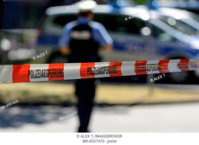 Police cordon with barrier tape, at back patrol cars and police officers, Frankfurt am Main, Germany