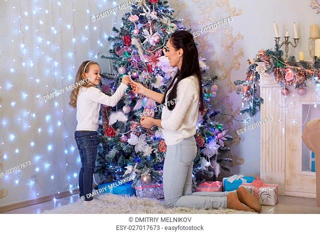 The pretty girl with mum are decorating a Christmas tree in the house. Happy family. Merry Christmas and New Year
