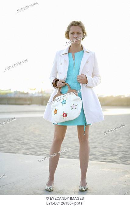 Young woman with handbag posing outdoors