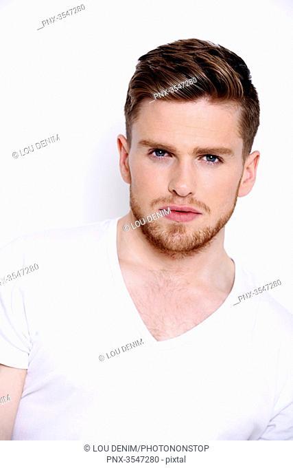 man in a white T-shirt, beard, serious, white background, studio